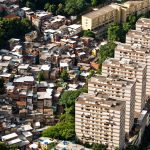 Urban dwelling/favela next to multi-family home illustrating the need to create affordable housing and upgrade urban dwellings